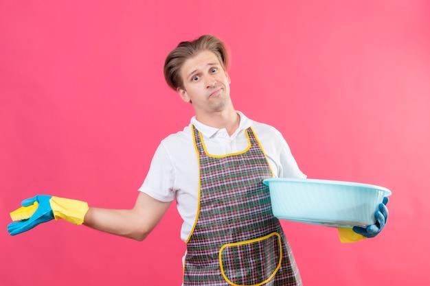 Молодой человек в фартуке и резиновых перчатках держит таз с чистящими средствами и выглядит смущенным