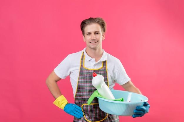 Молодой человек в фартуке и резиновых перчатках держит таз с чистящими средствами с уверенной улыбкой на лице, стоящим над розовой стеной
