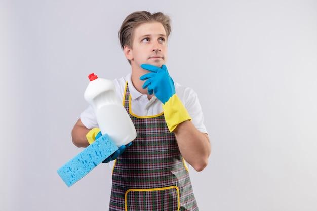 Молодой человек в фартуке и резиновых перчатках держит бутылку с чистящими средствами и губкой, глядя в сторону с рукой на подбородке с задумчивым выражением лица, думая, стоя над белой стеной