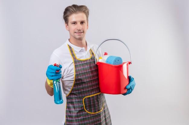 クリーニングツールでバケツを保持している自信を持って笑顔でスプレーを洗浄エプロンとゴム手袋を着用して若いhansdome男