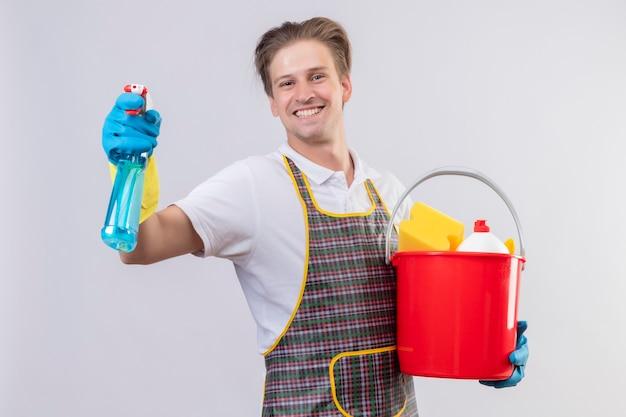 クリーニングツールとスプレーを洗浄するバケットを保持しているエプロンとゴム手袋を着用して若いhansdome男