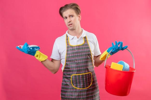 Молодой человек в фартуке и резиновых перчатках держит ведро с чистящими средствами и чистящим спреем