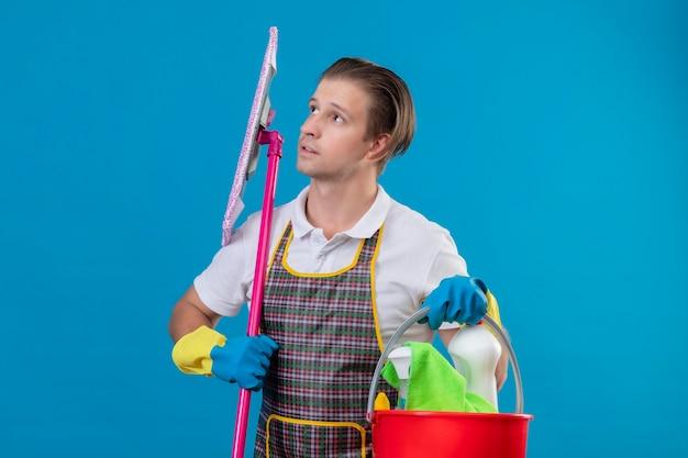 Молодой человек в фартуке и резиновых перчатках держит ведро с инструментами для уборки и шваброй, глядя в сторону с задумчивым выражением лица, стоя у синей стены
