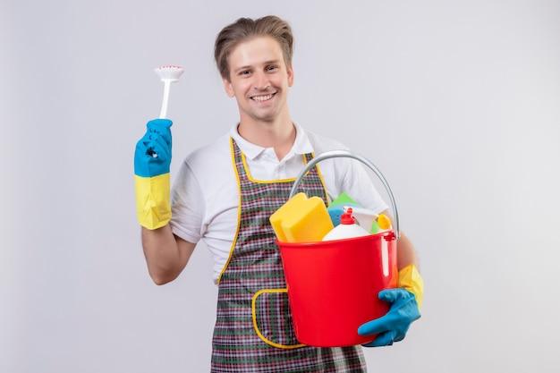 Молодой человек в фартуке и резиновых перчатках держит ведро с инструментами для чистки и чисткой