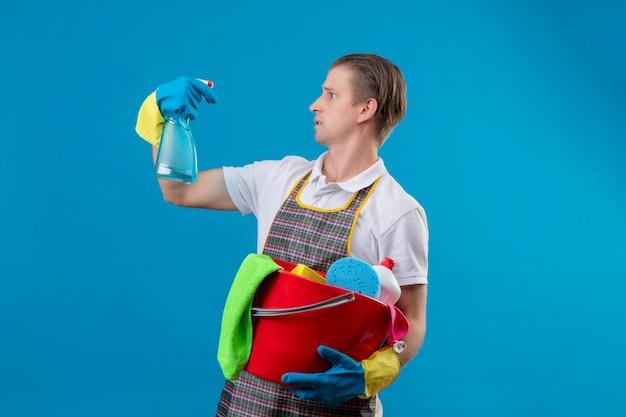 Молодой человек в фартуке и резиновых перчатках держит ведро с чистящими средствами