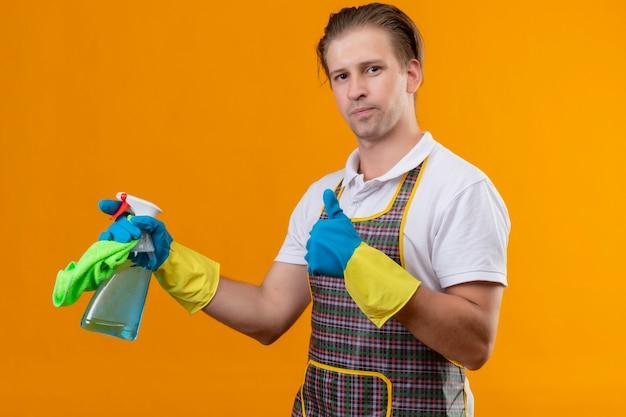 オレンジ色の壁の上に立っている親指を示す顔に自信を持って笑顔でクリーニングスプレーと敷物を保持しているエプロンとゴム手袋を着用して若いhansdome男