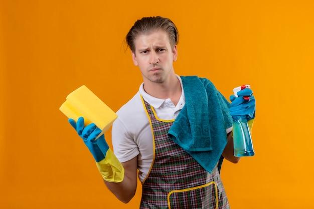Молодой человек в фартуке и резиновых перчатках держит чистящий спрей и губку, недовольный хмурым лицом, стоящим над оранжевой стеной