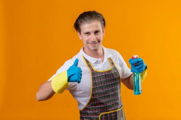 エプロンとゴム手袋をはめて若いhansdome男が立っているovewrオレンジの壁を親指を示す幸せと肯定的な笑みを浮かべてクリーニングスプレーを保持しているゴム手袋