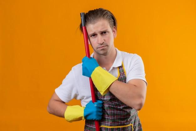 エプロンとモップを保持しているゴム手袋を着用して若いhansdome男が疲れてオレンジ色の壁の上に立って悲しそうな表情で働きすぎ