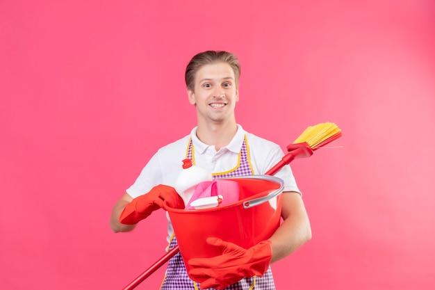 Молодой человек в фартуке держит ведро с чистящими средствами и шваброй, улыбаясь счастливым лицом, стоящим над розовой стеной