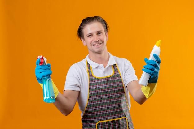 Giovane hansdome uomo che indossa un grembiule azienda spray per la pulizia e ru