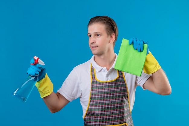 Giovane hansdome uomo che indossa un grembiule azienda spray per la pulizia e tappeto sorridente felice e positivo che guarda da parte pronto per pulire in piedi sopra la parete blu