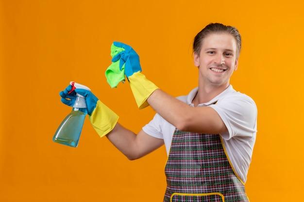 Giovane hansdome uomo che indossa il grembiule azienda spray per la pulizia e tappeto sorridente felice e positivo pronto a pulire in piedi sopra la parete arancione