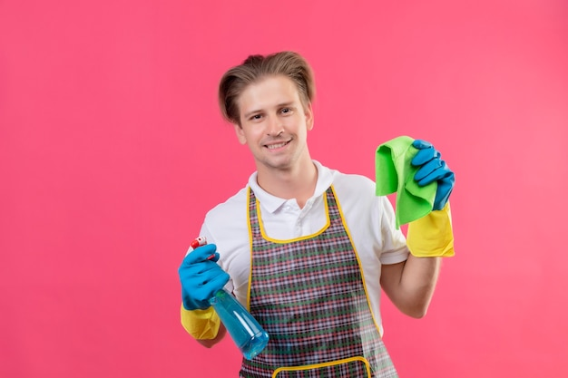 Young hansdome man wearing apron holding cleaning spray and rug happy and positive smiling ready to clean standing over pink wall