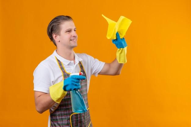 Giovane hansdome uomo che indossa un grembiule azienda spray per la pulizia e tappeto