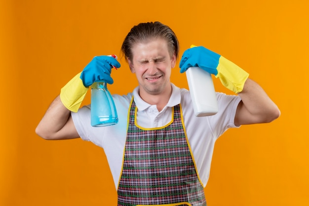 Young hansdome man wearing apron and rubber gloves holding bottles with cleaning supplies