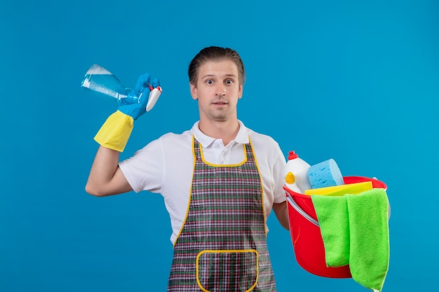 Young hansdome man wearing apron and rubber gloves holding bucket with cleaning tools