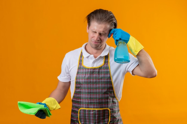 Young hansdome man wearing apron and rubber gloves holding cleaning spray and rug