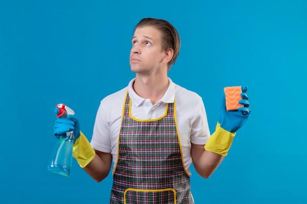 Giovane hansdome uomo che indossa un grembiule e guanti di gomma tenendo spray per la pulizia e spugna guardando da parte con espressione pensierosa sul viso in piedi sopra la parete blu