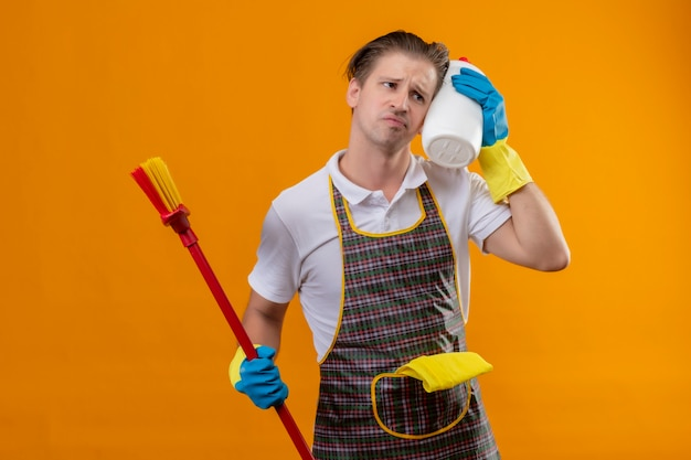 Young hansdome man wearing apron and rubber gloves holding mop and bottle of cleaning supplies