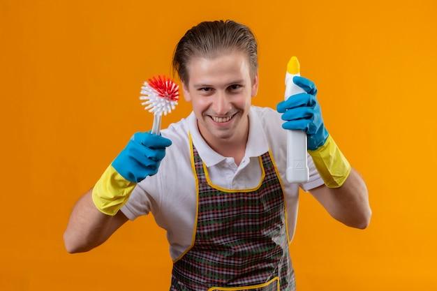 Grembiule da portare del giovane uomo di hansdome e guanti di gomma che tengono la spazzola e la bottiglia di sfregamento con i prodotti per la pulizia