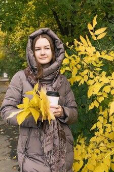 コーヒーと黄色の葉を持つ若い幸せの美しい少女秋の秋の色