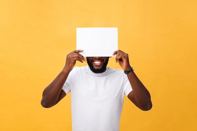 Молодой счастливый афроамериканец прячется за чистый лист бумаги, изолированных на желтом фоне