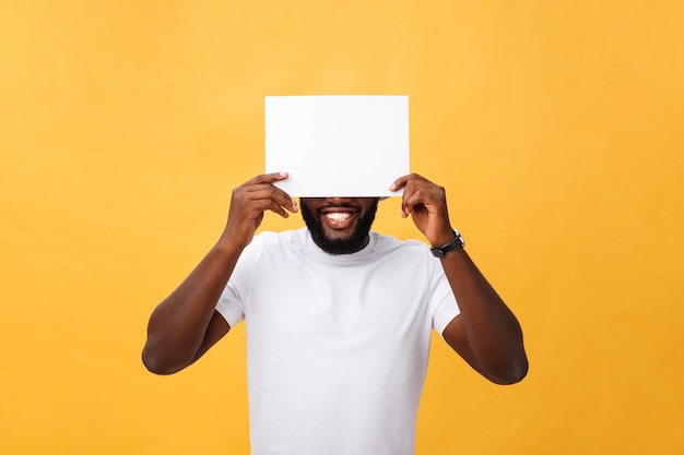 Young happy african-american hiding behind a blank paper, isolated on yellow background