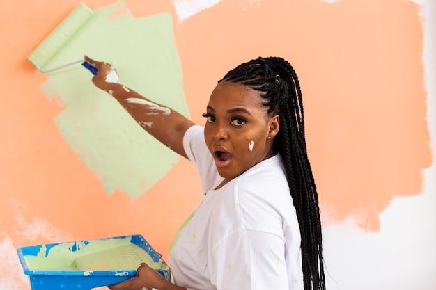 Молодая счастливая афро-американская женщина рисует внутреннюю стену валиком в новом доме. девушка
