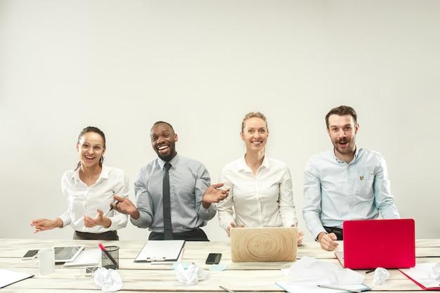 若い幸せなアフリカと白人の男性と女性のオフィスに座っているとラップトップに取り組んで。