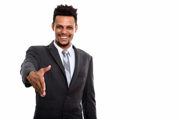 白で隔離の握手を与えながら笑っている若い幸せなアフリカのビジネスマン