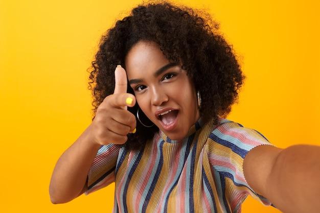 Молодая счастливая африканская милая девушка позирует изолированной над желтым пространством, делает селфи указывая.