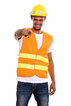 Young happy african man construction worker smiling while pointing at camera