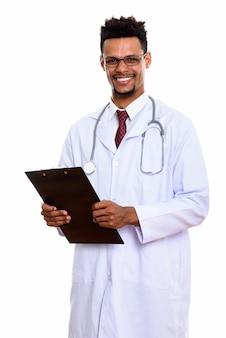 白で隔離クリップボードを保持しながら笑っている若い幸せなアフリカ人男性医師