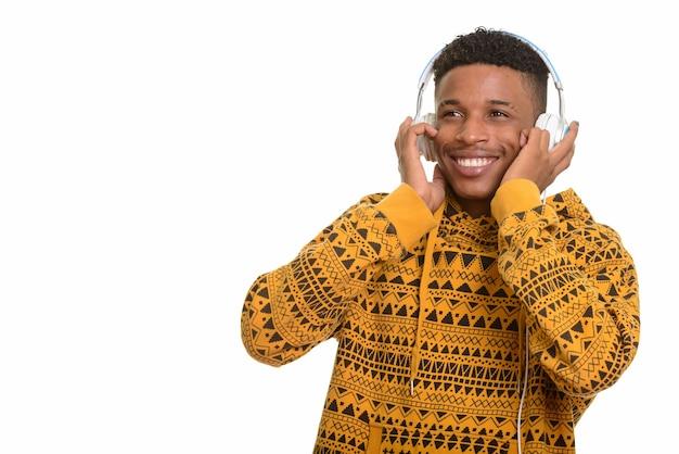 Молодой счастливый африканский человек слушает музыку, думая