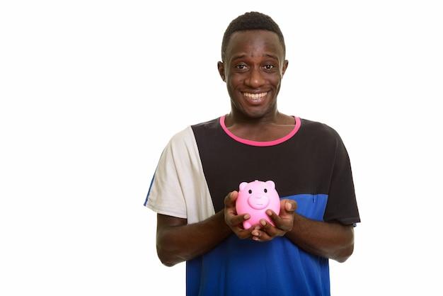 Молодой счастливый африканец улыбается и держит копилку