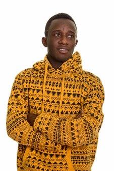 考えながら腕を組んで笑っている若い幸せなアフリカ人