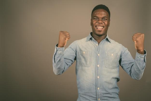 Молодой счастливый африканец улыбается с поднятыми руками