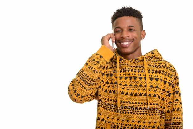 携帯電話で話している若い幸せなアフリカ人