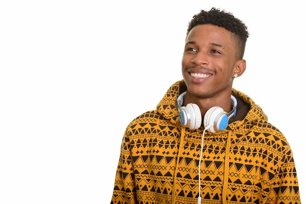 Young happy african man wearing headphones around neck while thi