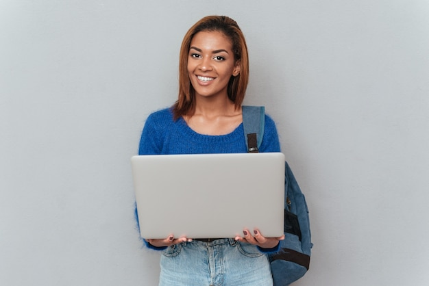 手にラップトップを保持しているバックパックとセーターとジーンズの若い幸せなアフリカの女性。孤立した灰色の背景
