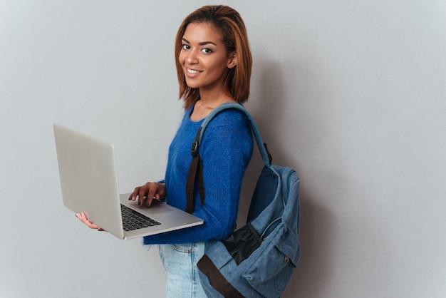 横に立っている手でラップトップを保持しているバックパックとセーターとジーンズの若い幸せなアフリカの女性