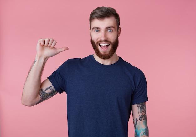 젊은 행복 놀란 매력적인 붉은 수염 젊은 남자, 파란색 티셔츠를 입고 광범위하게 smilimg, 분홍색 배경 위에 고립 된 자신을 가리키는 손가락.