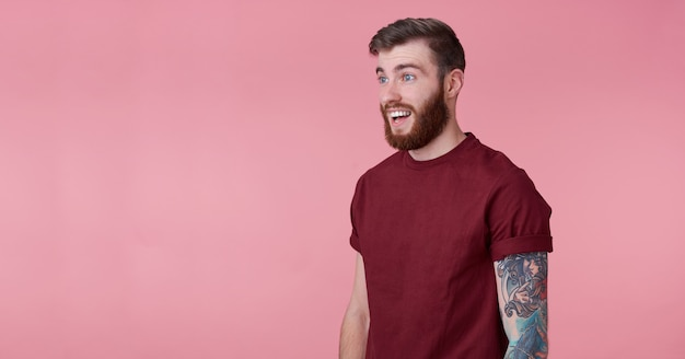 Young happy amazedred bearded man in blank t-shirt, looks to copy space on the left side, looks surprised, stands over pink background and broadly smiling.