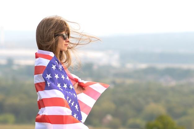 Молодая счастливая американская женщина с длинными волосами, держащая размахивая на ветру национальный флаг сша на ее плечах, расслабляющихся на открытом воздухе, наслаждаясь теплым летним днем.