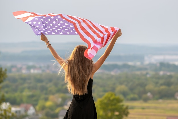 Young happy american woman with long hair raising up waving on wind usa national flag.