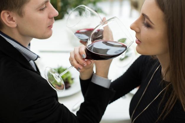 レストランで赤ワインを祝う若い幸せな好色なカップル。兄弟愛