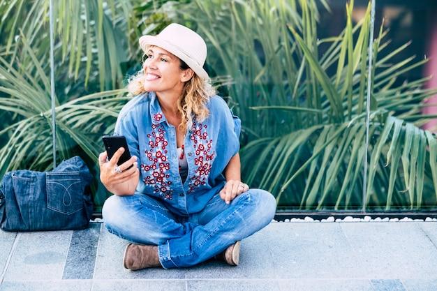 若い幸せで陽気な大人の女性は、屋外のレジャー活動で地面に座ります-現代人の簡単なライフスタイルは、携帯電話からビデオ通話の友人を使用します