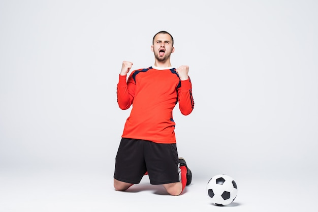Молодой счастливый и взволнованный футболист в майке празднует забитый гол