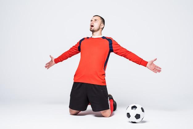 Молодой счастливый и взволнованный футболист в красной майке празднует забитый гол